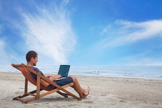 man reading laptop on a beach